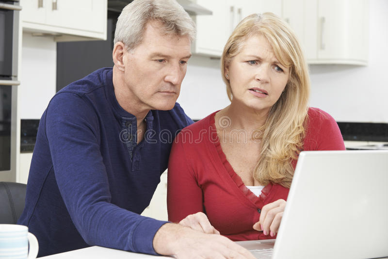 Worried Mature Couple Reviewing Domestic Finances. Worried Couple Reviewing Domestic Finances royalty free stock image