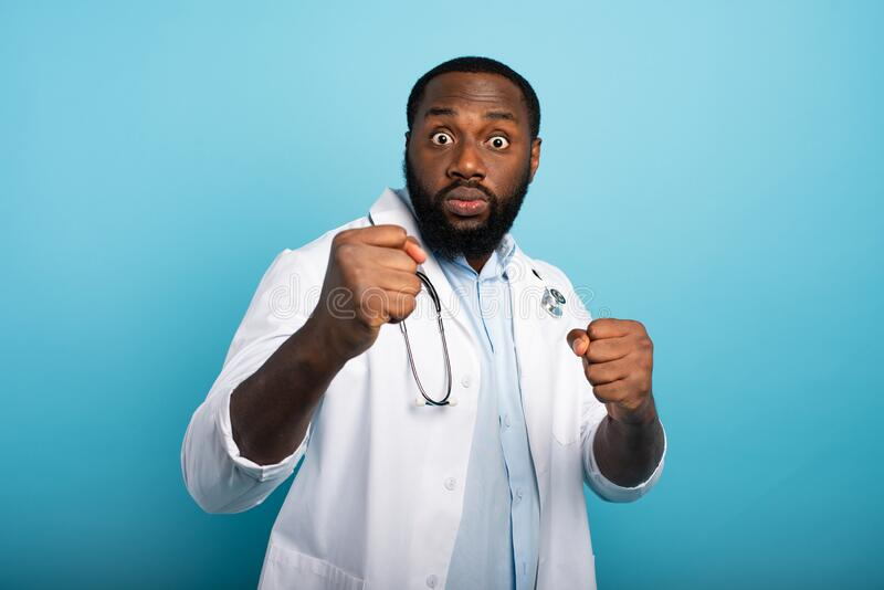 Worried medic is attacked by covid-19 coronavirus. Blue background royalty free stock photography
