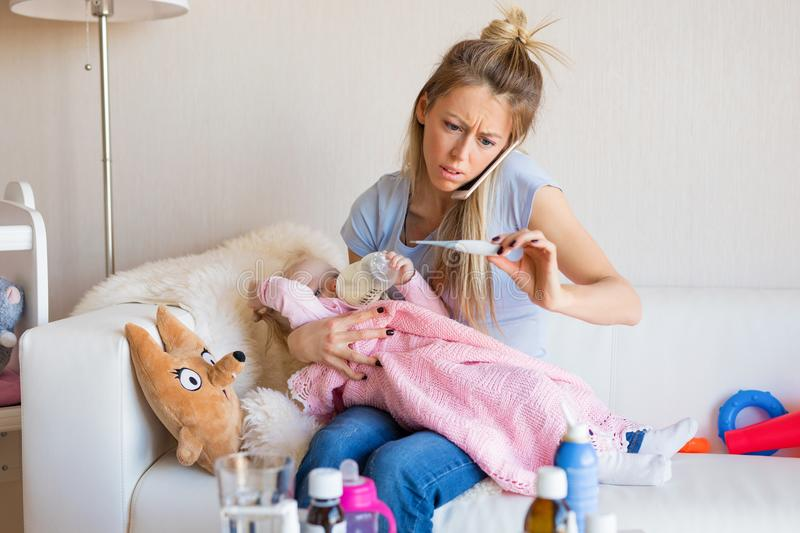 Worried mother with sick baby calling doctor royalty free stock photography