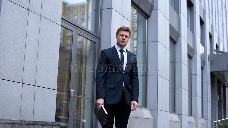 Worried office manager standing outdoors holding documents, unhappy worker stock images