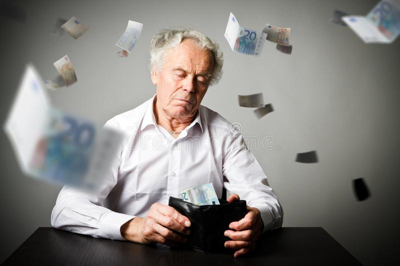 Old man in white and wallet with twenty Euro. Accounting and tax. Worried old man in white is looking at a twenty euro and wallet. Accounting and taxes concept stock image