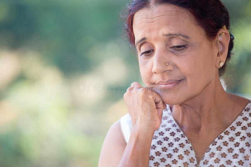 Worried old woman. Closeup portrait, morose elderly lady, downcast gloomy, resting face on hand, isolated green outdoors background stock photos