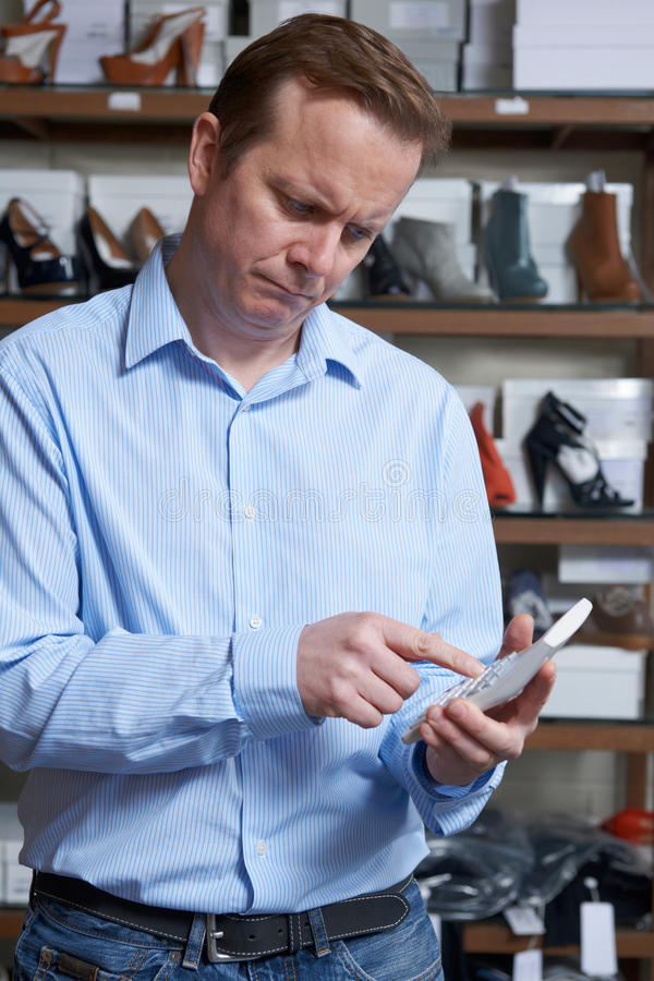 Worried Owner Of Shoe Store With Calculator stock photos