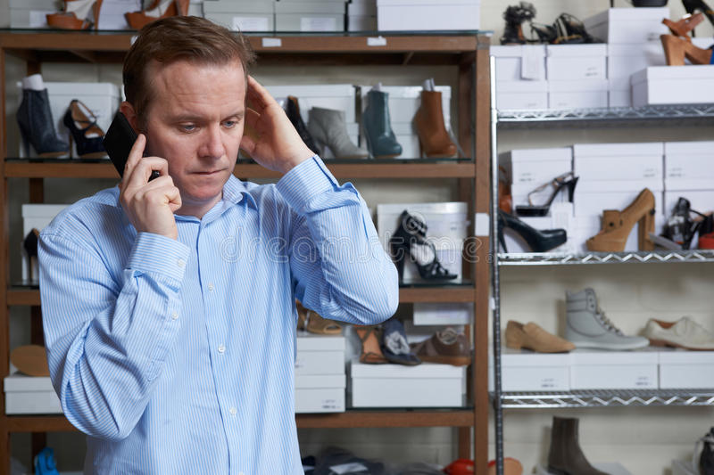 Worried Owner Of Shore Store On Phone stock image
