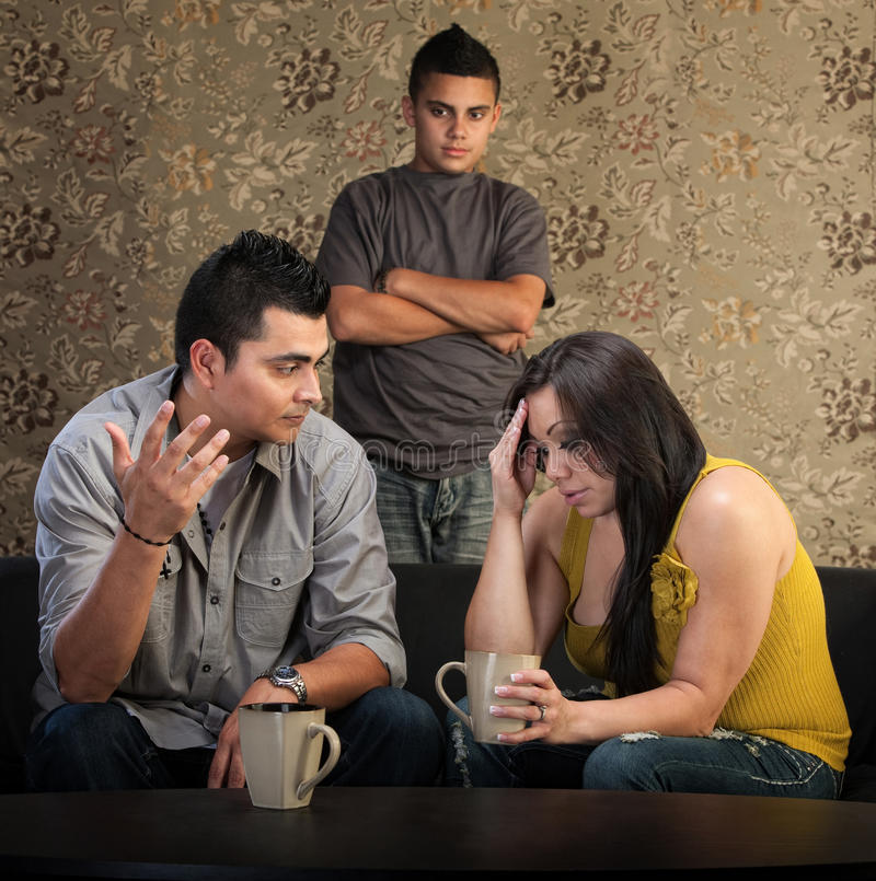 Worried Parents With Angry Son. Worried Native American couple with upset son indoors stock photo