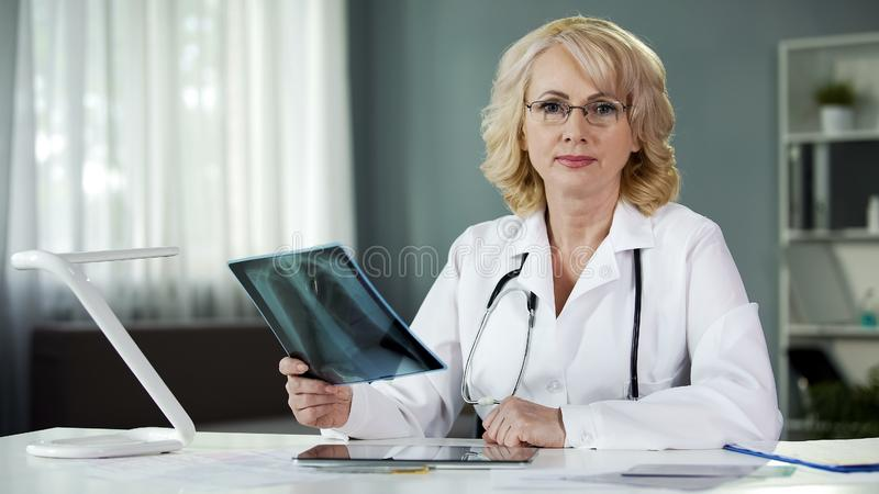 Worried about patient's health doctor seriously looking into camera, medicine royalty free stock image