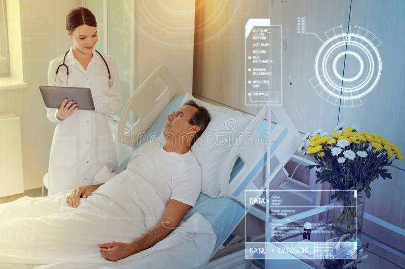 Worried patient staying in hospital bed and a kind doctor smiling to him royalty free stock images