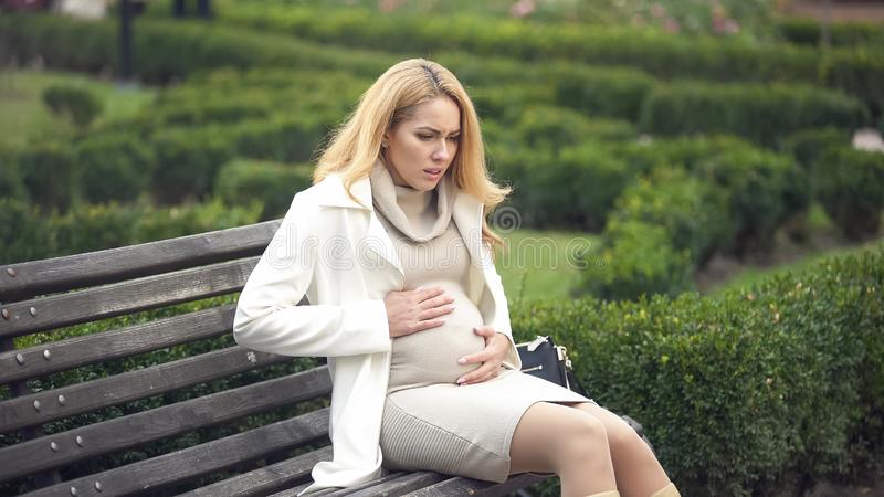 Worried pregnant lady breathing deeply, sitting bench, tummy ache, contractions. Stock photo stock photo