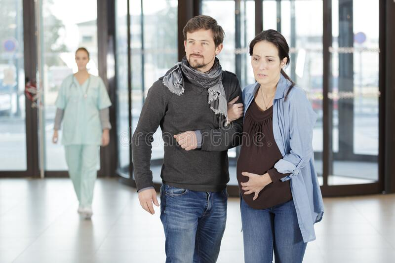 Worried pregnant woman and husband at hospital lobby royalty free stock photography