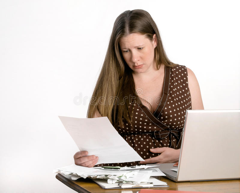 Worried Pregnant Young Woman Reading Bills at Lapt royalty free stock photo