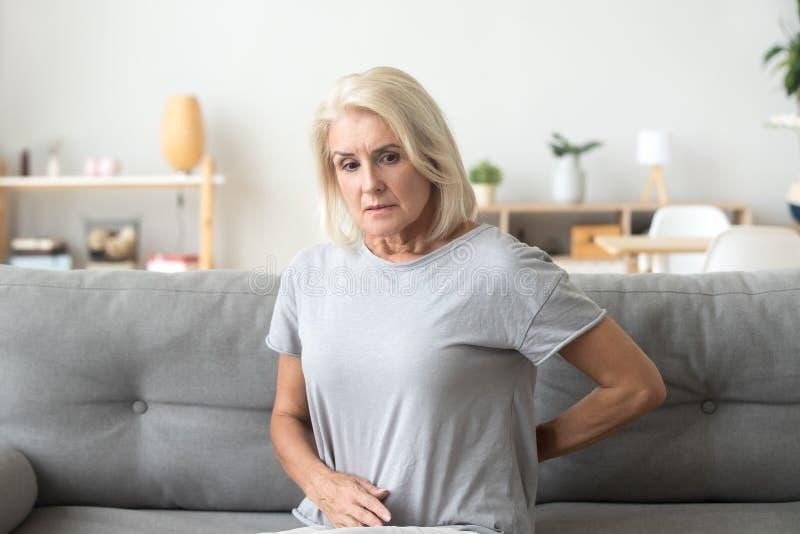 Worried sad older woman touching back feeling back pain stock photo
