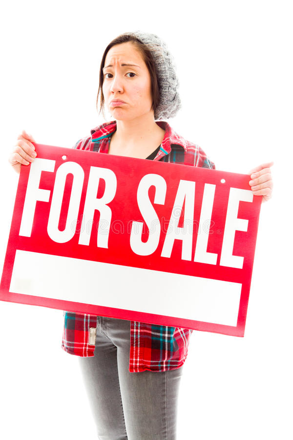Worried saleswoman showing a for sale sign. Young adult caucasian woman isolated on a white background stock image