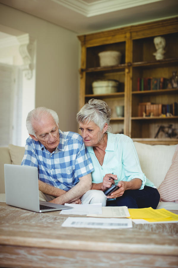 Worried senior couple checking bills in living room stock photography