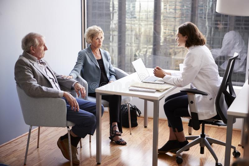 Worried Senior Couple Having Consultation With Female Doctor In Hospital Office royalty free stock photo