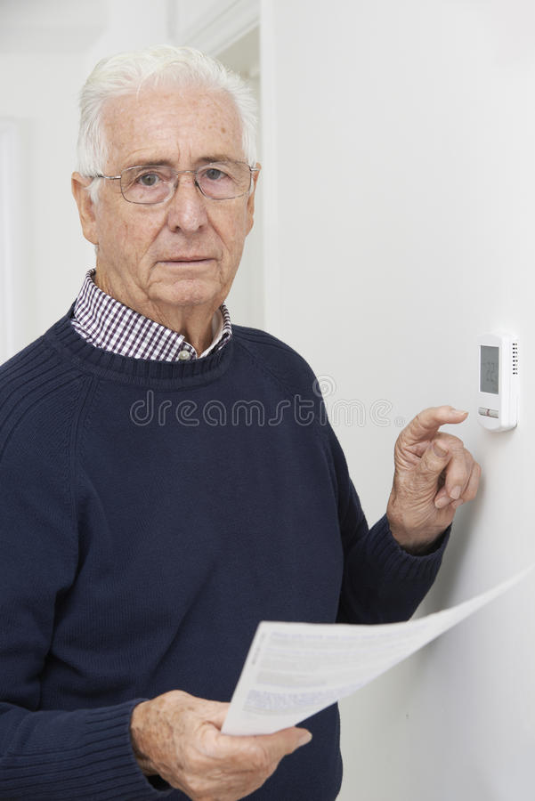 Worried Senior Man With Bill Turning Down Central Heating Thermostat. Portrait Of Worried Senior Man With Bill Turning Down Central Heating Thermostat stock photo