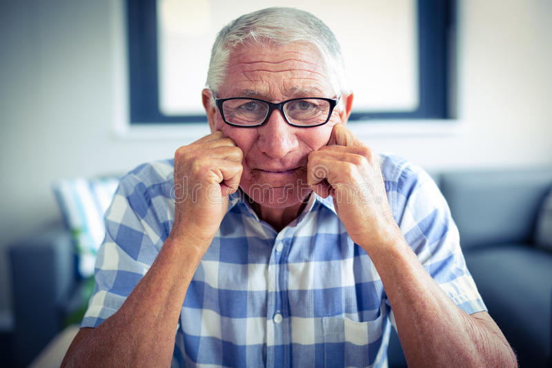 Worried senior man sitting in living room. At home stock photography