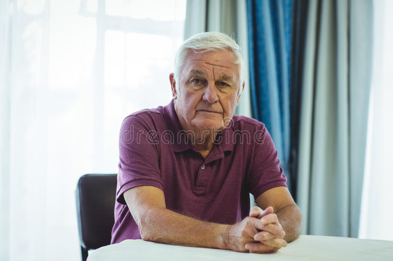 Worried senior man sitting beside table stock image