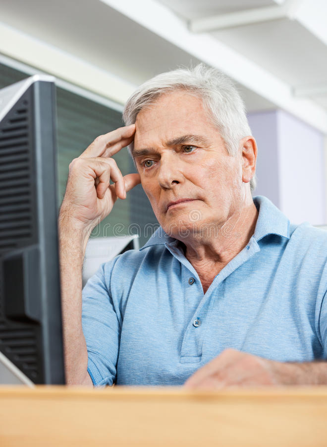 Worried Senior Student Looking At Computer In Class stock photo