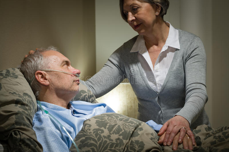 Worried senior woman caring with sick husband royalty free stock image