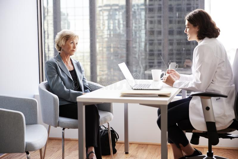 Worried Senior Woman Having Consultation With Female Doctor In Hospital Office royalty free stock photography