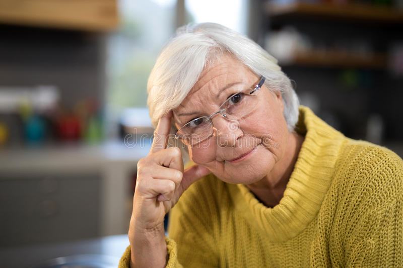 Worried senior woman in the kitchen stock photo