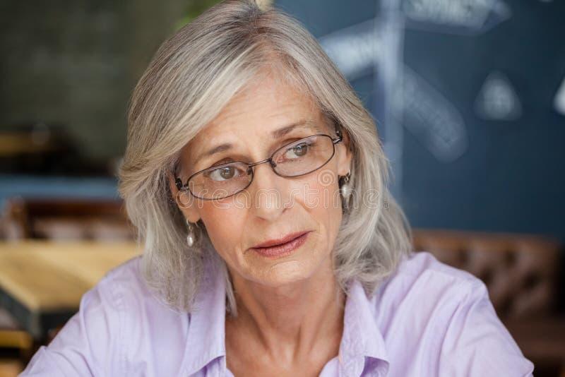 Worried senior woman looking away stock images