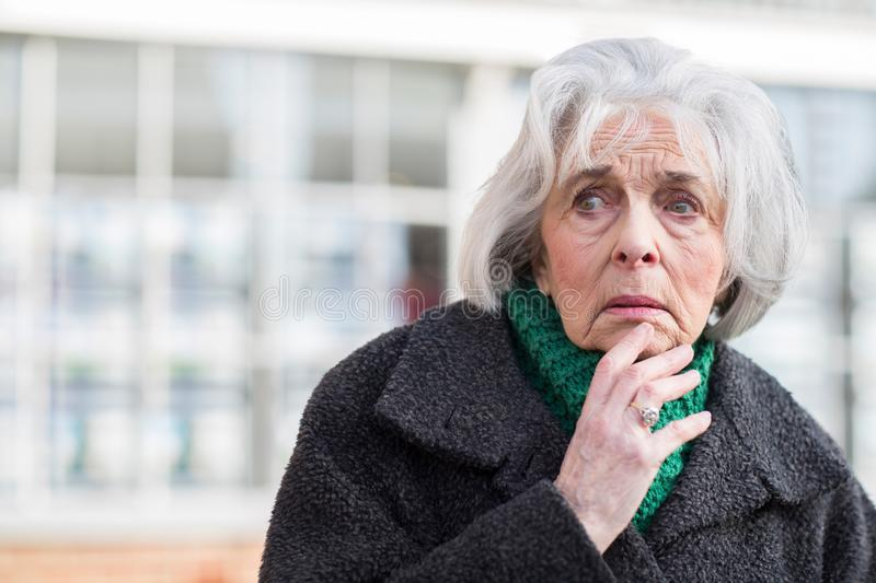 Worried Senior Woman Looking Lost Outdoors royalty free stock image