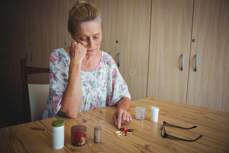 Worried senior woman with medics on the table stock photography