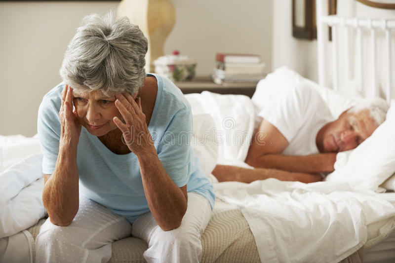 Worried Senior Woman Sits On Bed Whilst Husband Sleeps royalty free stock photo
