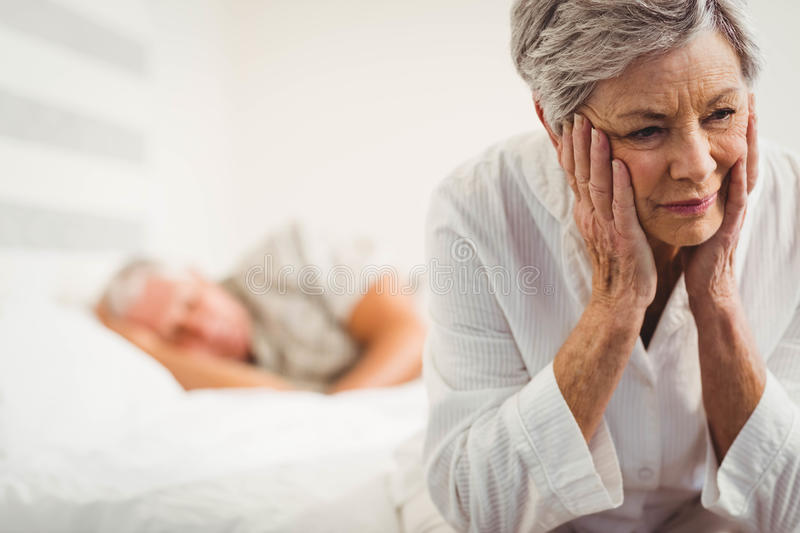 Worried senior woman sitting on bed royalty free stock image