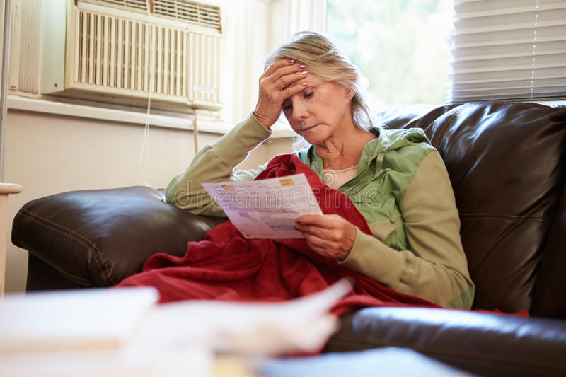Worried Senior Woman Sitting On Sofa Looking At Bills stock photos