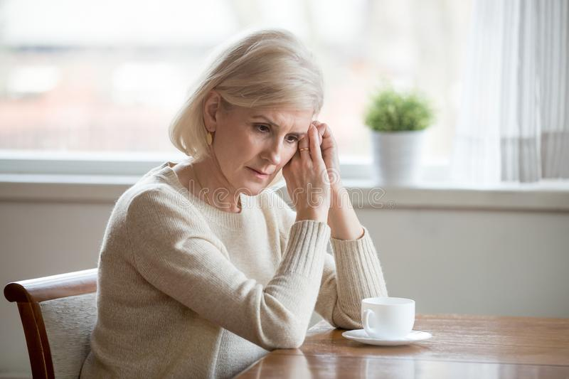 Concerned aged woman sit at table lost in thoughts. Worried senior woman sitting at table at home lost in thoughts, concerned aged female distracted from reality stock images