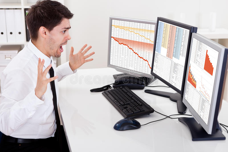 Worried stock broker. Looking at stock charts going down stock photography
