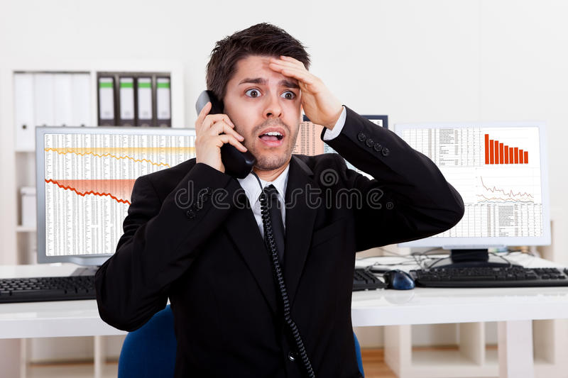 Worried stock broker on the phone. Worried stock broker talking on the phone backed by graphs depicting a crisis stock image