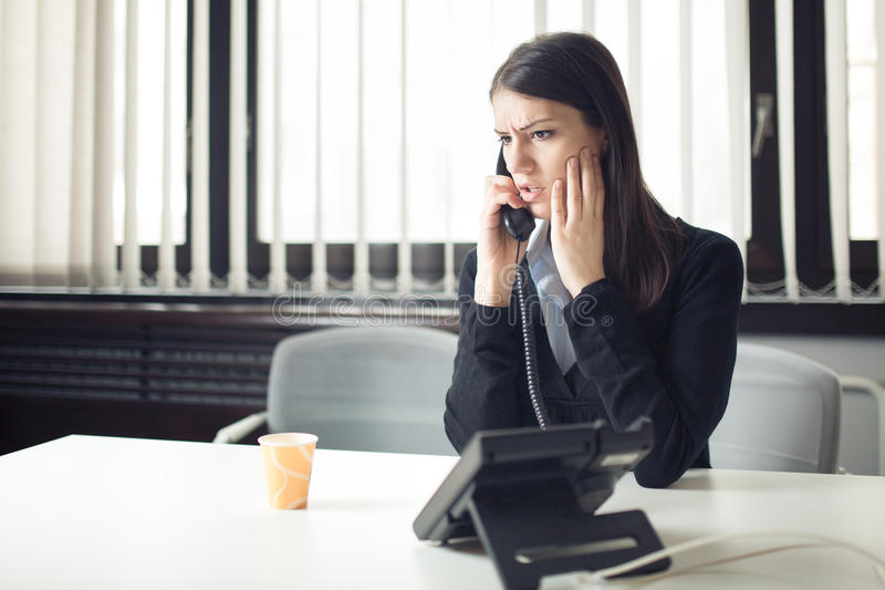 Worried stressed depressed office worker business woman receiving bad news emergency phone call at work. Looking confused stock photography