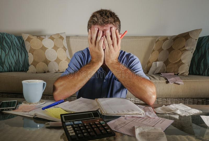 Attractive worried stressed man at home calculating month tax expenses with calculator accounting payments doing bank paperwork in royalty free stock images