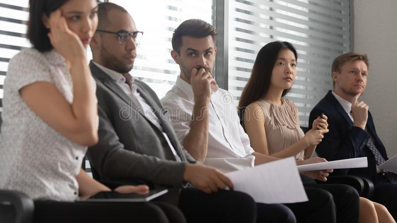 Worried stressed mixed race people applicants sitting in queue. royalty free stock image