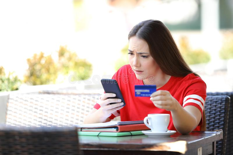 Worried student paying online with credit card in a bar royalty free stock images