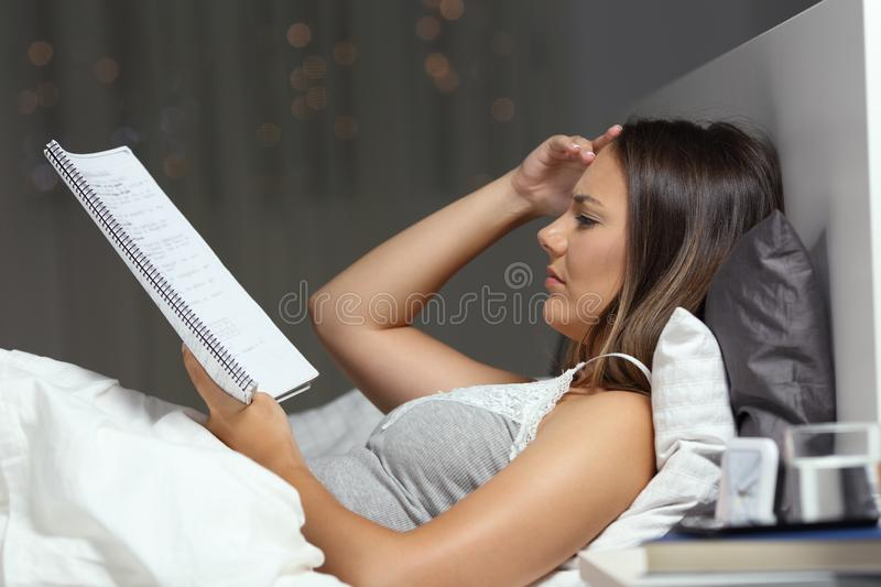 Worried student studying late hours in the bed at home. Side view portrait of a worried student studying late hours in the bed at home royalty free stock images