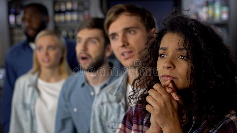 Worried team supporters watching tv competition, group of fans at sport event stock photo