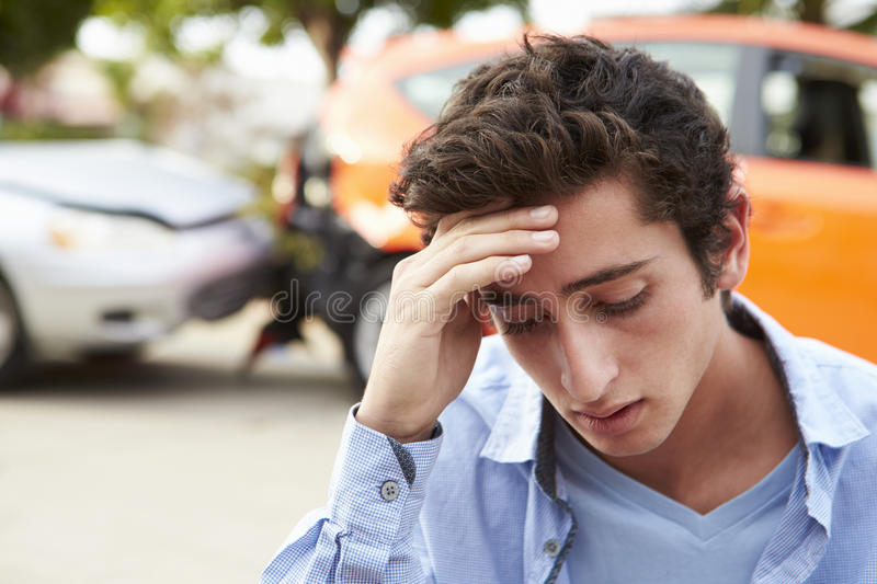 Worried Teenage Driver Sitting By Car After Traffic Accident stock photo