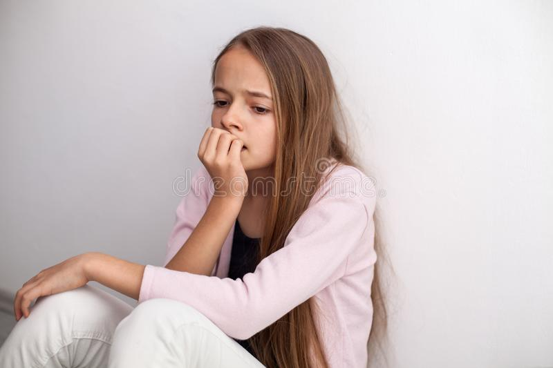 Worried teenage girl biting her nails sitting on the floor by th. E wall - looking agitated royalty free stock image
