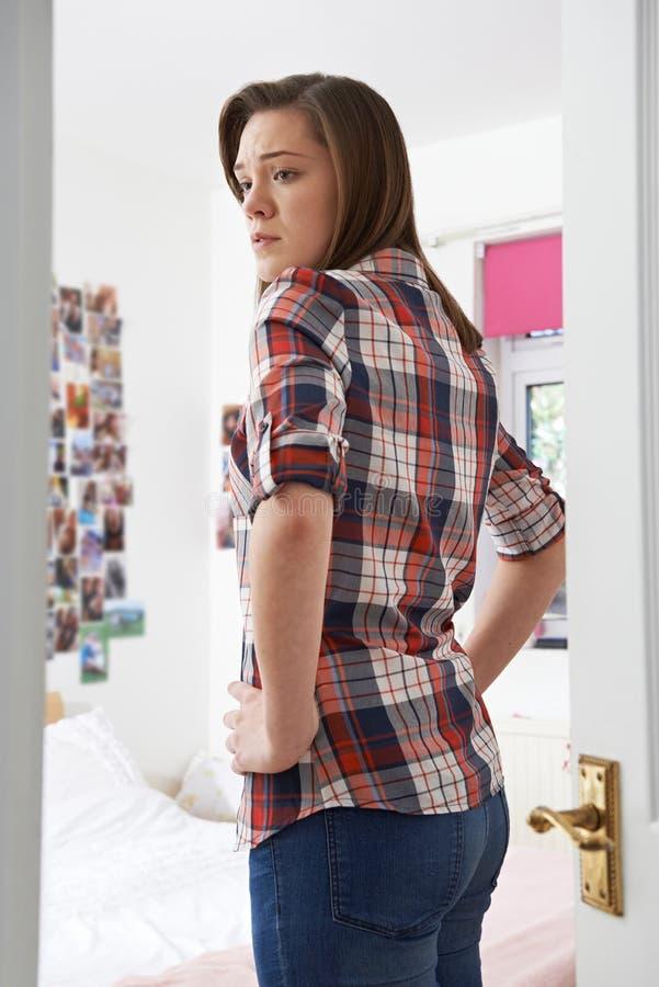 Worried Teenage Girl Looking At Reflection In Bedroom Mirror stock photos