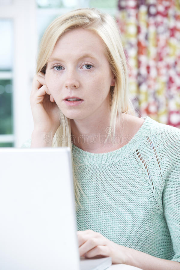 Worried Teenage Girl Using Laptop At Home. Portrait Of Worried Teenage Girl Using Laptop At Home royalty free stock photography