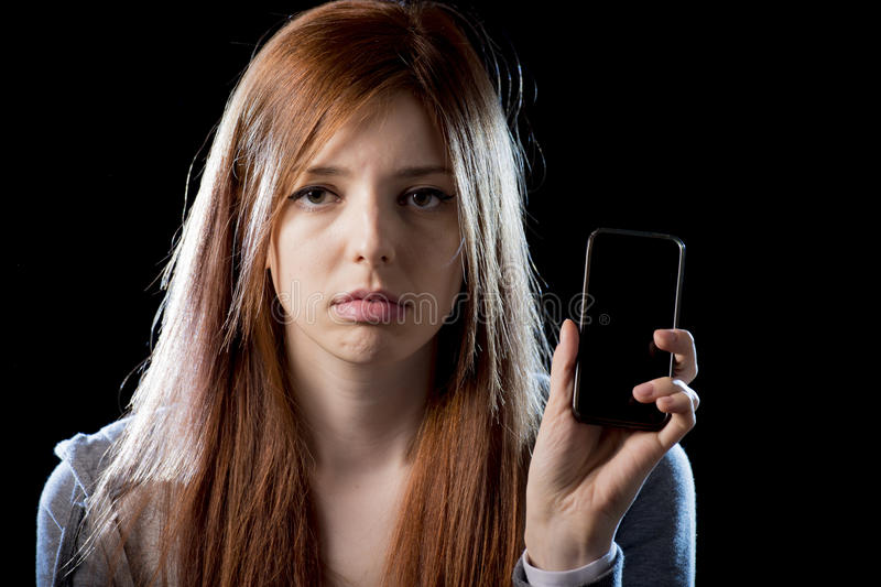 Worried teenager holding mobile phone as internet cyber bullying stalked victim abused. Young scared and worried teenager girl holding mobile phone as internet royalty free stock photo
