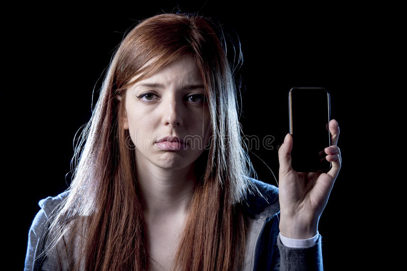 Worried teenager holding mobile phone as internet cyber bullying stalked victim abused. Young scared and worried teenager girl holding mobile phone as internet royalty free stock image