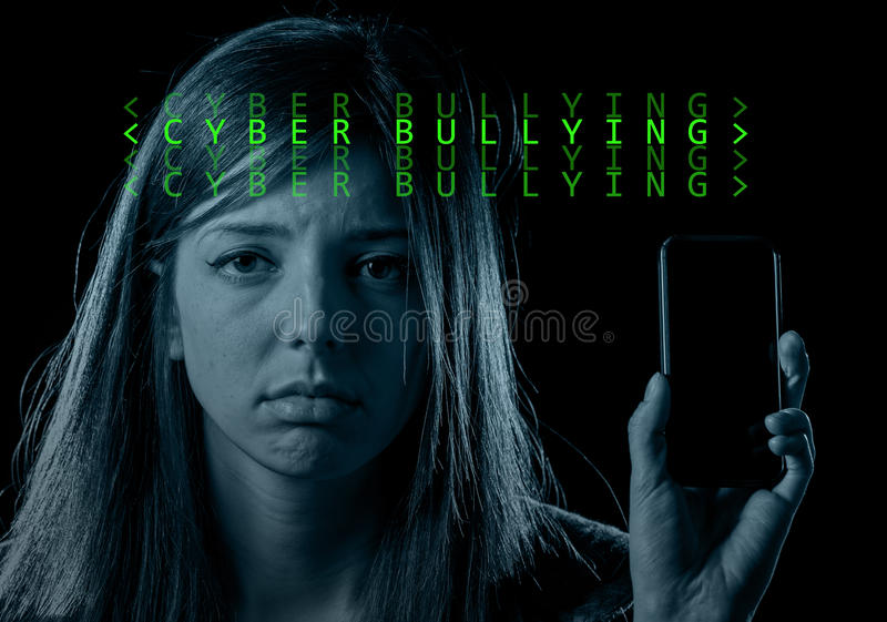 Worried teenager holding mobile phone as internet cyber bullying. Young scared and worried teenager girl holding mobile phone as internet stalked victim abused stock image