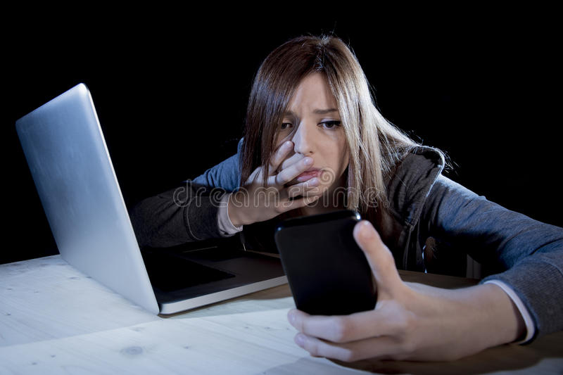 Worried teenager using mobile phone and computer as internet cyber bullying stalked victim abused. Young scared and worried teenager girl using mobile phone and royalty free stock photo