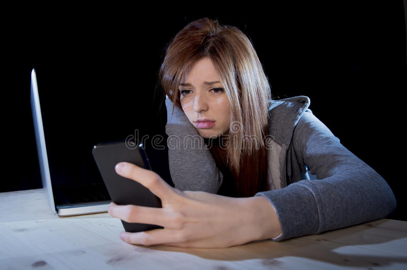 Worried teenager using mobile phone and computer as internet cyber bullying stalked victim abused. Young scared and worried teenager girl using mobile phone and stock photos