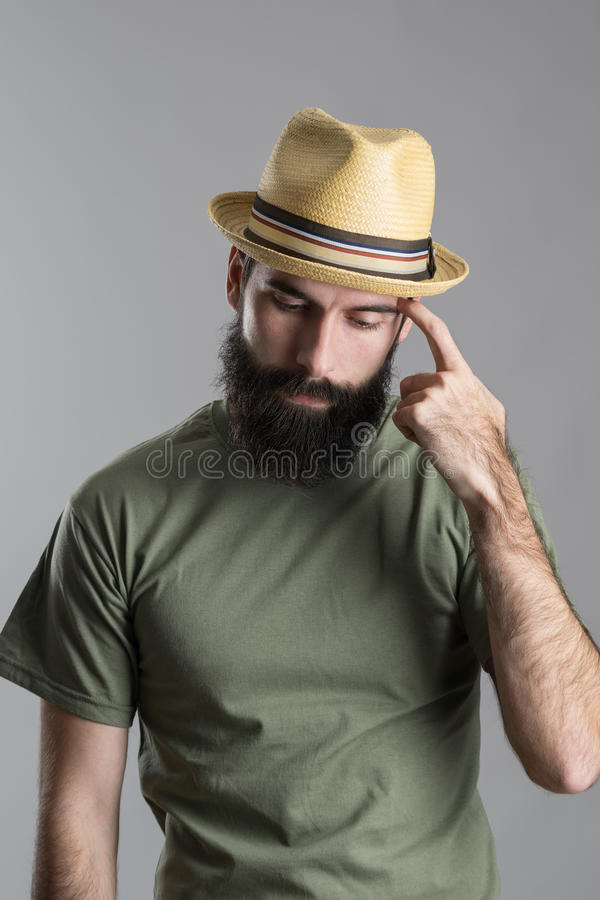 Worried thinking bearded man wearing straw hat looking down and scratching hand with finger. Portrait over gray studio background royalty free stock photo